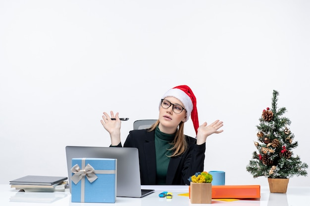 Confused curious blonde woman with a santa claus hat sitting at a table with a christmas tree and a gift on it in the office on white background