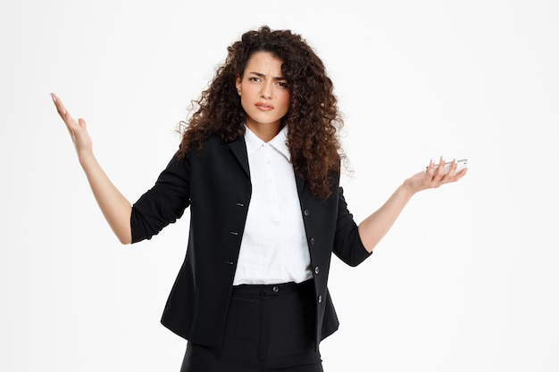 Confused curly business girl holding phone