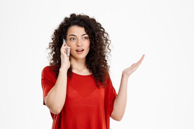 彼女の電話で話している混乱している巻き毛の少女