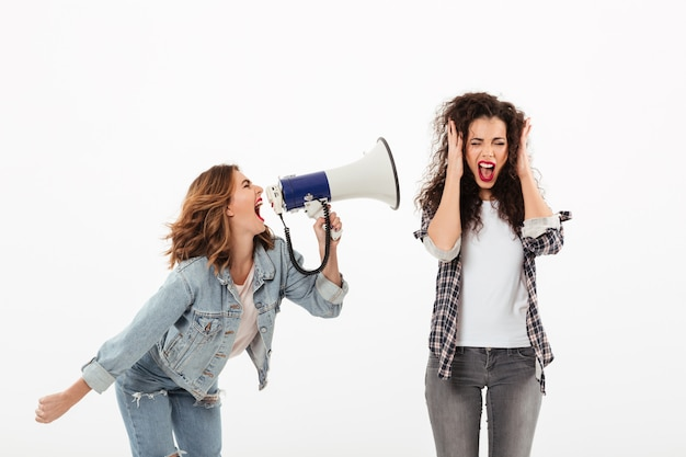 Confused curly woman covering her ears while second girl screaming at her with megaphone over white wall
