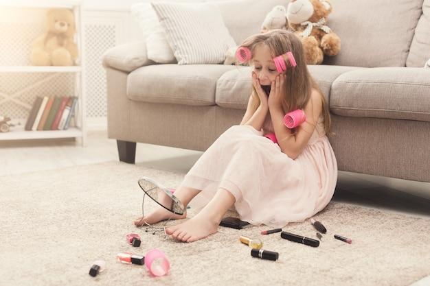 化粧品をしようとしているヘアカーラーの混乱したかわいい女の子。たくさんの美容製品の中で床に座って、驚きを持って鏡を見て、初めてメイクをして、スペースをコピーするかわいい子供