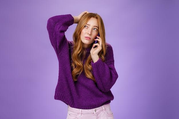 Confuso femmina rossa carina che fa appuntamento tramite telefono cellulare grattandosi la nuca e strizzando gli occhi, guardando in alto come pensando di fare una scelta o ricordare, parlando con lo smartphone sul muro viola.