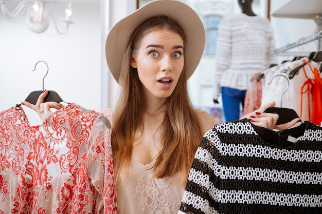 Confused cute woman doing shopping and choosing dress in clothing store