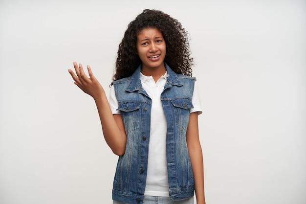 Donna riccia bruna dalla pelle scura confusa che alza il palmo perplesso e aggrotta la fronte mentre posa su bianco in maglia di jeans e camicia bianca