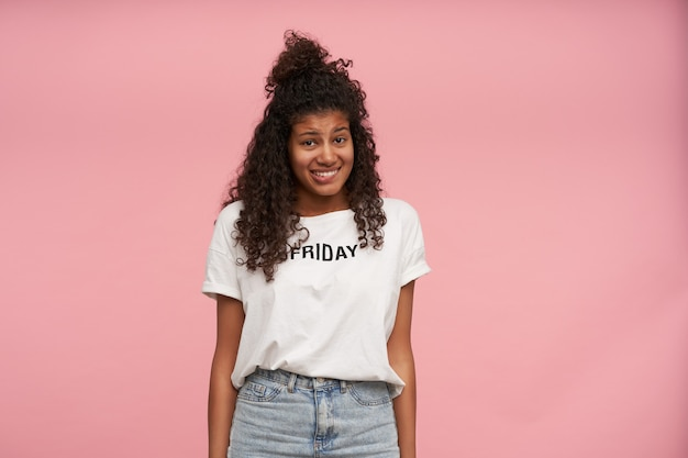 Confused dark skinned curly brunette female with oops face and biting underlip, keeping hands along body while posing on pink, dressed in casual clothes