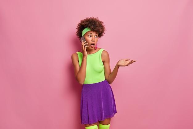 Смущенная темнокожая женщина с шокированным выражением лица, говорит по мобильному телефону, недоверчиво смотрит, поднимает ладонь, носит летний наряд.