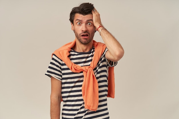 어깨에 줄무늬 티셔츠와 스웨터에 강모가있는 혼란스러운 멍청한 젊은 남자가 머리와 입에 손을 계속 열어 둡니다.