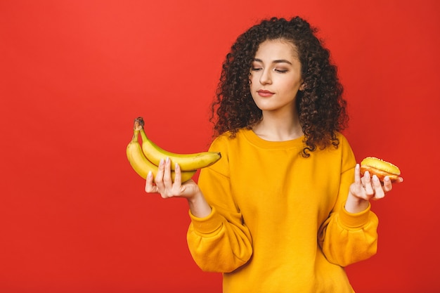 Confused deciding between healthy and unhealthy food, she is holding fruits and donut on her hands, isolated on red background.