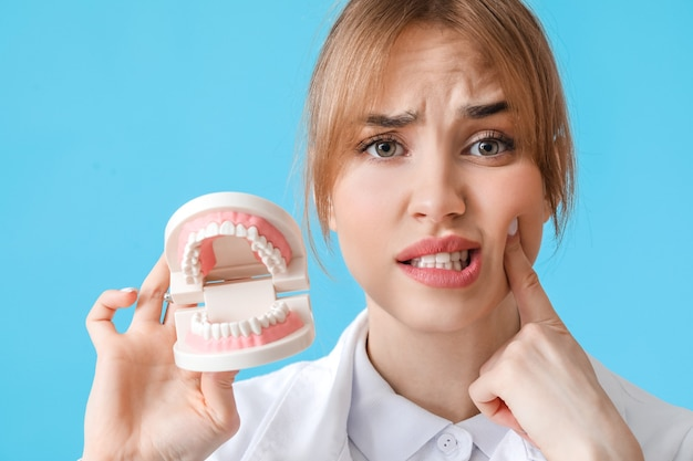 Confused dentist with plastic jaw model on color surface