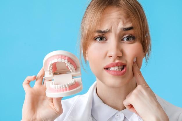 Смущенный стоматолог с пластиковой моделью челюсти на цветной поверхности