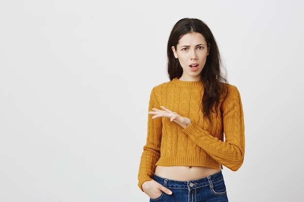 Confused and disappointed girl arguing, raising hand puzzled, asking question