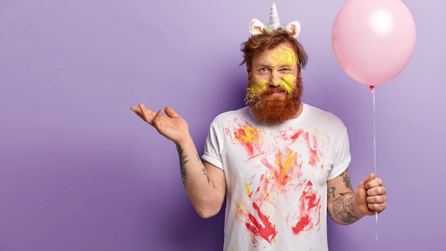 Confused discontent red haired man with bristle, raises palm and smirks face, being entertainer on holiday, wears unicorn horn and untidy white t shirt with traces of watercolours, isolated on purple