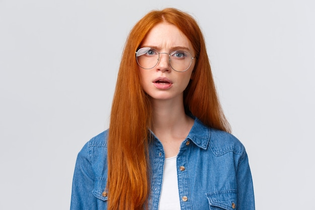 Confused and displeased, unsure redhead girl in glasses having conversation, talking look frustrated and slightly unconvinced, have doubts standing white  frowning