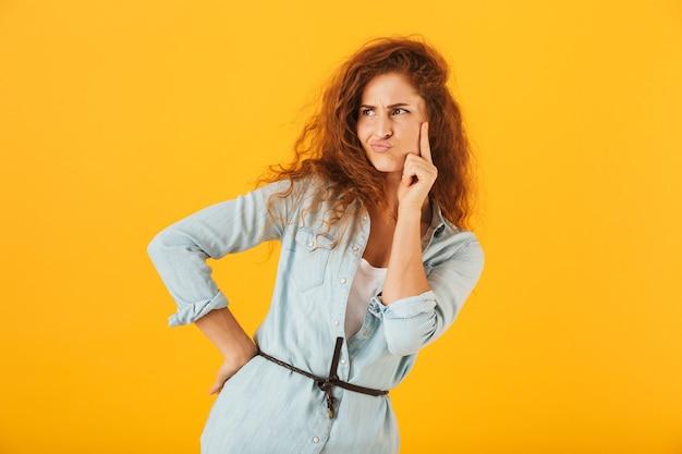 Смущенная недовольная женщина думает и смотрит в сторону, изолированную на желтом фоне