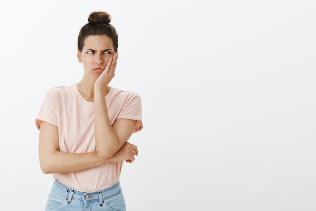 Confused and displeased young stylish woman posing against the white wall