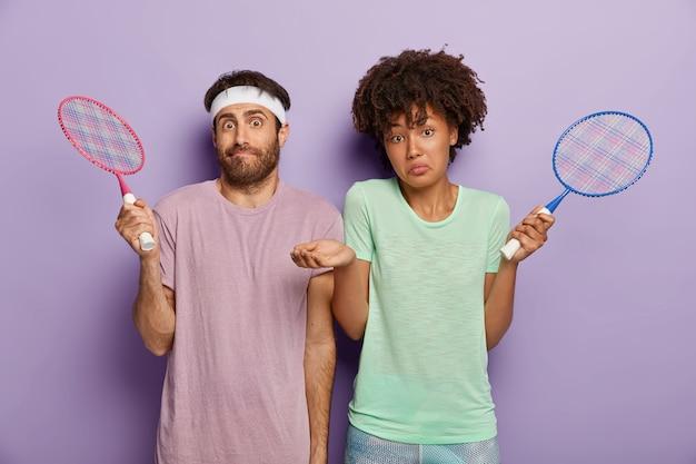 혼란스러워하는 다양한 여자와 남자 테니스 선수들이 라켓을 들고 서 있고, 알지 못하는 표정을 가지고 있으며, 보라색 벽에 고립 된 티셔츠를 입은 코트를 찾을 수 없습니다. 좋아하는 게임 컨셉