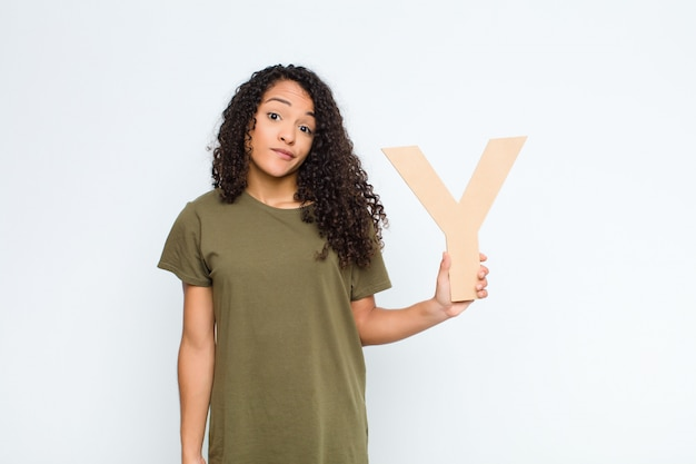Confused, doubtful, thinking, holding the letter y of the alphabet to form a word or a sentence.