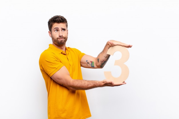 Confused, doubtful, thinking, holding a number 3.