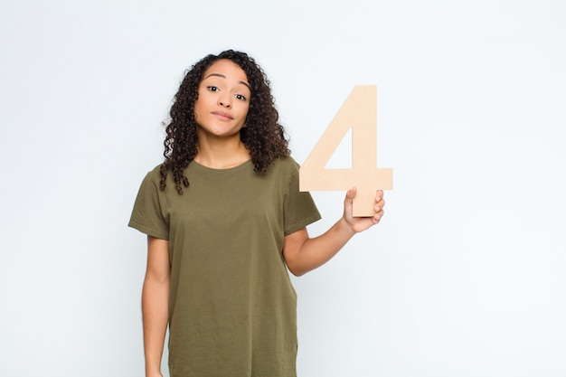 Confused, doubtful, thinking, holding a number 4.