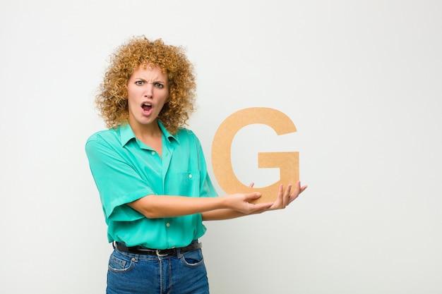 Запутанный, сомнительный, думающий, держа букву g алфавита, чтобы сформировать слово или предложение.