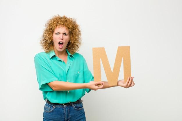 Запутанный, сомнительный, думающий, держа букву м алфавита, чтобы сформировать слово или предложение.