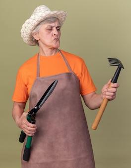 정원용 가위를 들고 정원용 모자를 쓰고 복사 공간이 있는 올리브 녹색 벽에 격리된 갈퀴를 바라보는 혼란스러운 노인 여성 정원사