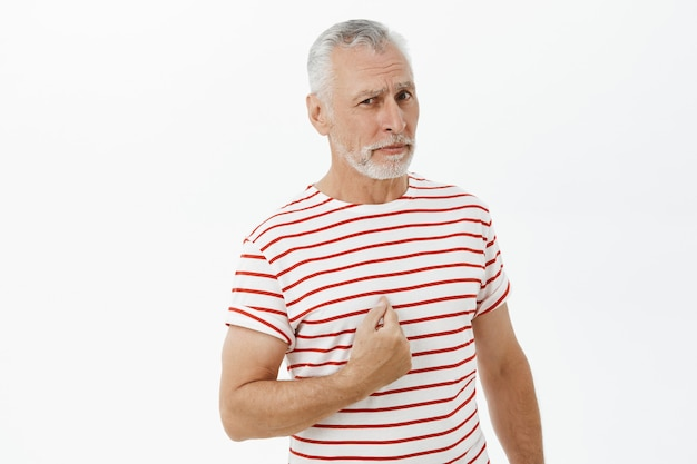 Confused elderly man pointing at himself puzzled