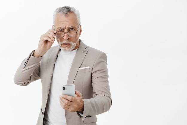 Confused elderly man in suit holding mobile phone and looking