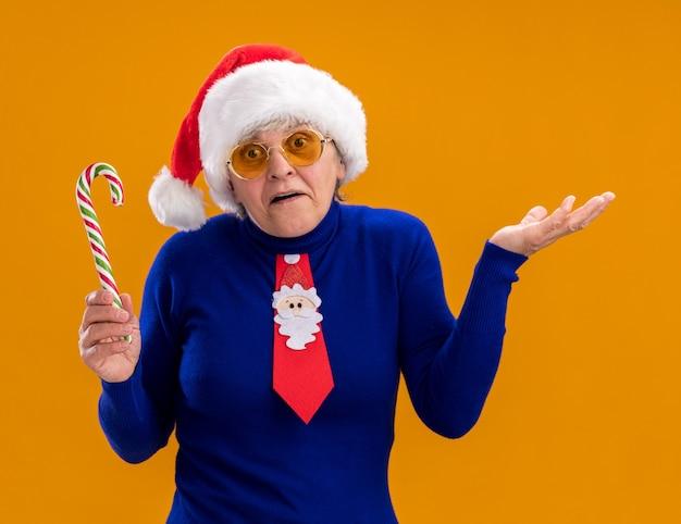 Donna anziana confusa in occhiali da sole con cappello da babbo natale e cravatta di babbo natale che tiene un bastoncino di zucchero e tiene la mano aperta isolata sulla parete arancione con spazio di copia