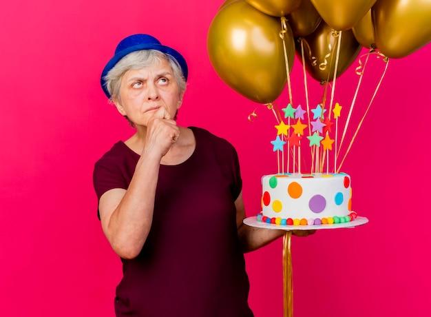 La donna anziana confusa che porta il cappello del partito tiene i palloni dell'elio e la torta di compleanno che mette la mano