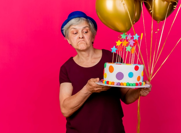 Confused elderly woman wearing party hat holds helium balloons and looks at birthday cake on pink