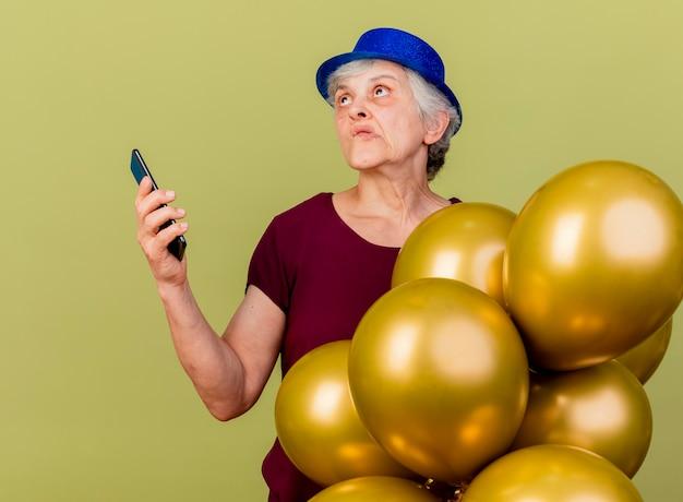 パーティーハットを身に着けている混乱した年配の女性は、コピースペースのあるオリーブグリーンの壁に隔離された電話を見上げるヘリウム気球で立っています