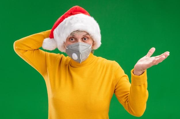 医療マスクを身に着けているサンタの帽子をかぶった混乱した年配の女性は、頭に手を置き、コピースペースのある緑の壁に隔離された手を開いたままにします。
