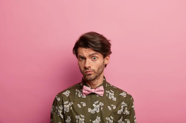 Uomo europeo confuso con l'acconciatura alla moda guarda direttamente la telecamera, indossa una camicia verde con papillon, isolato su un muro roseo