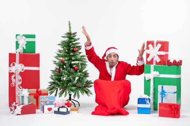 혼란 스 러 워 흥분된 젊은 남자 선물 산타 클로스로 옷을 입고 흰색 배경에 바닥에 앉아 장식 된 크리스마스 트리
