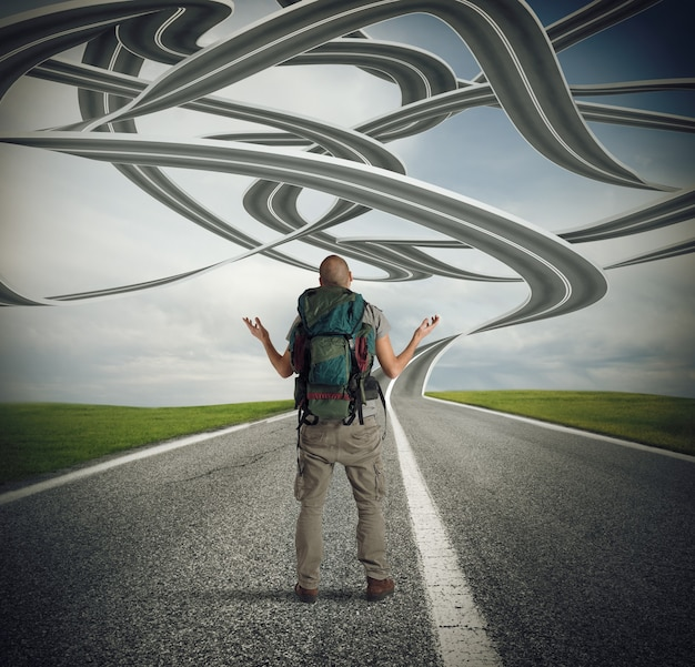 Confused explorer man before a winding road
