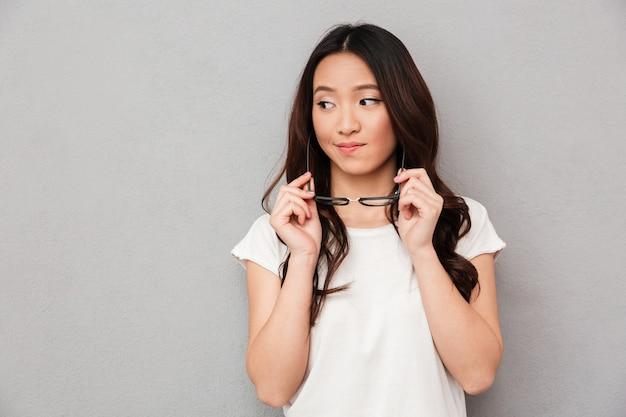 Confused азиатская женщина в футболке держа eyeglasses и смотря прочь