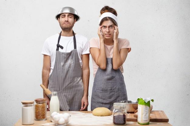 La donna confusa tiene le mani sulle tempie, cerca di ricordare la ricetta,