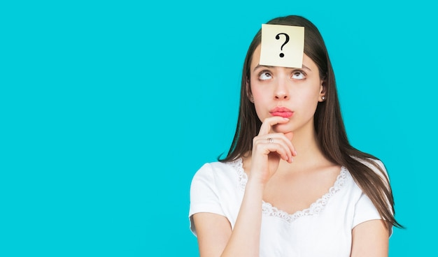 Confused female thinking with question mark on sticky note on forehead.