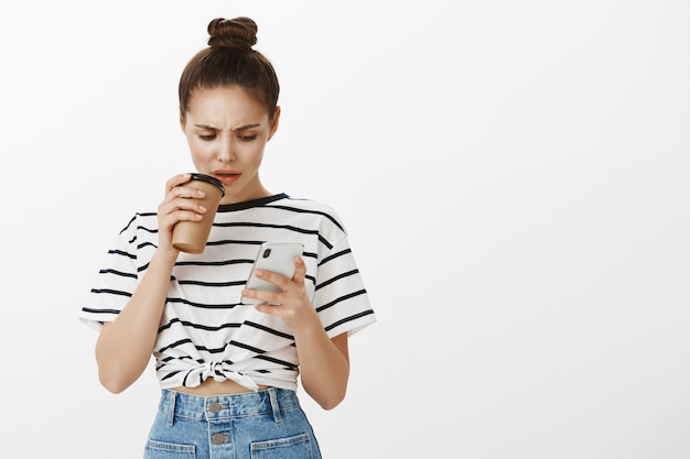 Confused frowning girl looking at mobile phone screen while making sip of coffee from cup