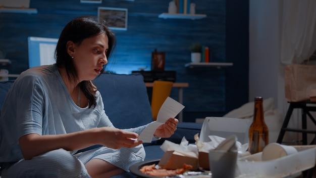 Смущенная и разочарованная молодая женщина, читающая письмо о долге, плохой финансовый отчет, деньги, п ...