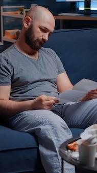 Смущенный, разочарованный, подчеркнутый молодой человек, читающий письмо с уведомлением о долге, плохой финансовый отчет, деньги, р ...
