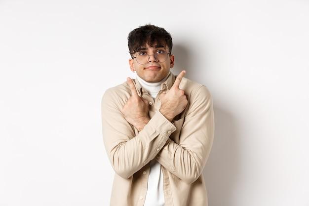 眼鏡をかけたおかしな男が指を脇に向けて混乱し、2つのバリエーションを示し、白い背景の上に立って、優柔不断に見えます。