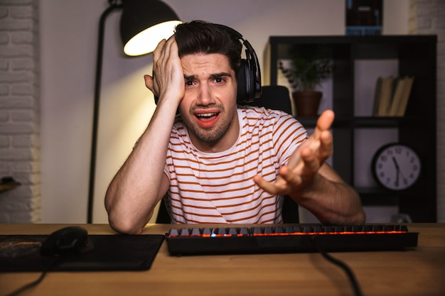 Confused gamer playing video games on computer