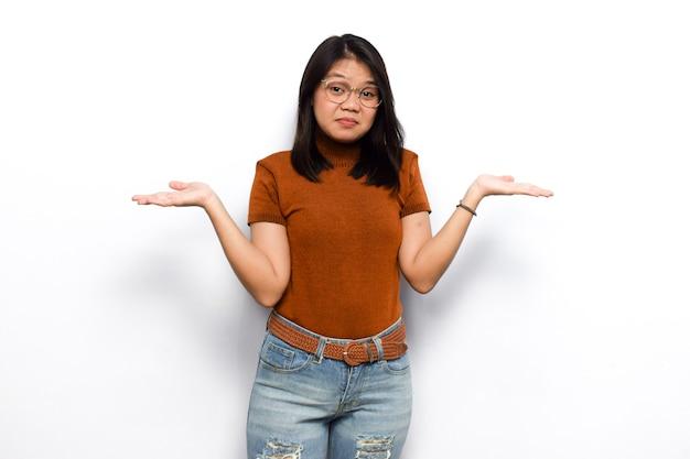 흰색 배경에 격리된 주황색 셔츠를 입은 아름다운 아시아 여성의 혼란스러운 제스처