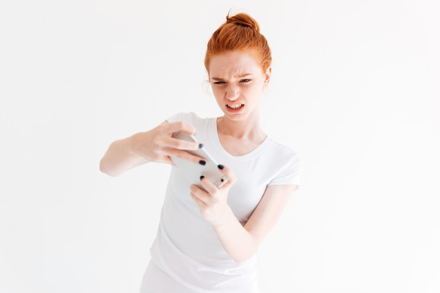 Confused ginger woman in t-shirt playing on her smartphone