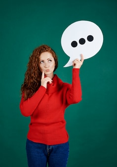 Confused girl holding speech bubble and looking at copy space