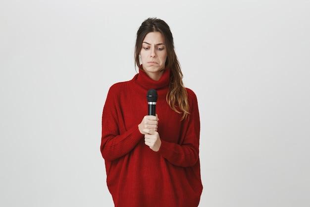 Смущенная девушка, выглядящая озадаченной в микрофоне