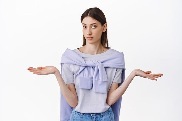 混乱した少女が手を横に広げて肩をすくめる、言うまでもなく、何が起こったのかわからない、白い壁に質問されて立っている