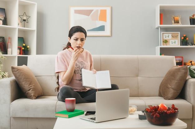 Mento afferrato confuso giovane ragazza che tiene il taccuino seduto sul divano dietro il tavolino da caffè guardando il computer portatile in soggiorno